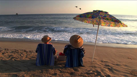 A couple under an umbrella on the beach make a toast and... Stock Video Footage