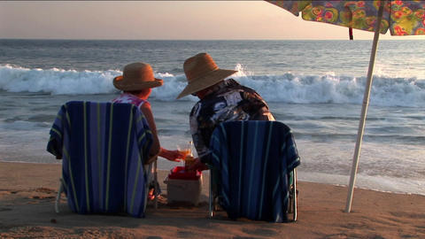 An elderly couple share drinks under an umbrella on the... Stock Video Footage