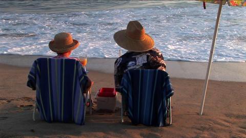 An elderly couple share drinks under an umbrella on the beach Footage