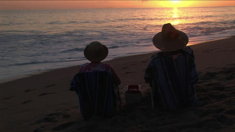 A couple toasts the ocean from their beach chairs Stock Video Footage