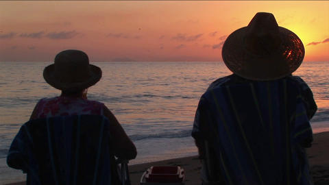 A couple toasts the ocean as they sit on a beach Stock Video Footage