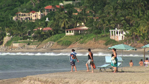 Three people walk to the water at a beach resort Stock Video Footage