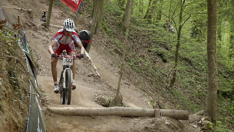 Cyclist race along a rough dirt road course Footage