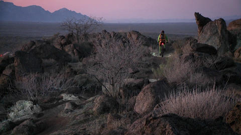 Cyclists travel rough trails in a desert area near dusk... Stock Video Footage