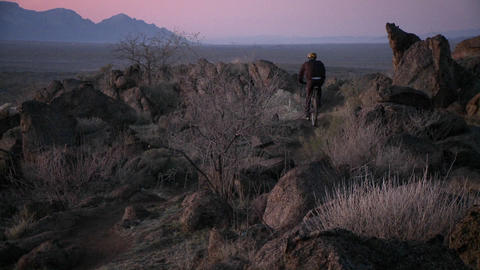 Cyclists travel rough trails in a desert area near dusk with head lights Footage