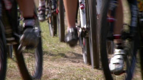 Dozens of bikers race on a rough course terrain Stock Video Footage