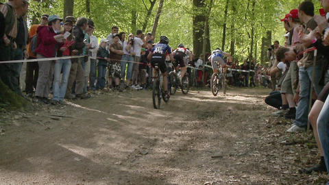 Bicyclists race as a crowd watches Live Action