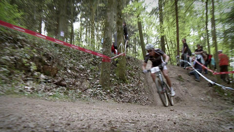 Bicyclists race through the woods as people watch Stock Video Footage