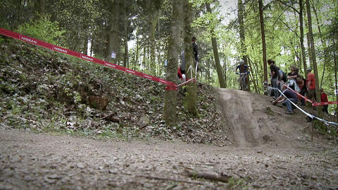 Bicyclists race through the woods as people watch Footage