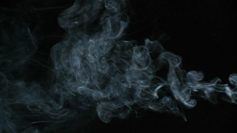 Cigarette smoke is being blown in against a black background Stock Video Footage