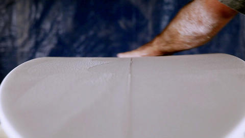 A craftsman is planning down a custom surfboard Stock Video Footage