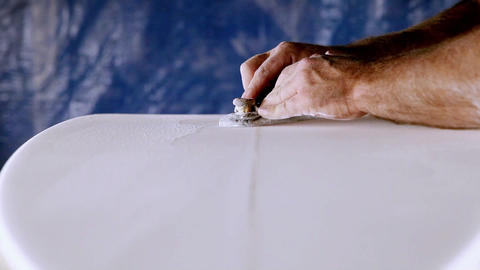 A craftsman is planning down a custom surfboard Footage