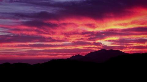 A man climbs a mountain as the sun sets Stock Video Footage