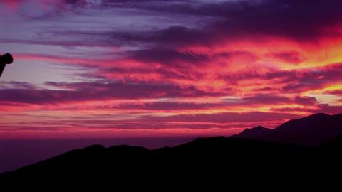A man climbs a mountain as the sun sets Footage