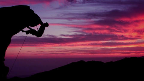 A man climbs a mountain as the sun sets Stock Video Footage