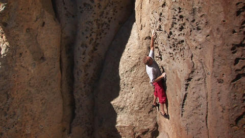 A man climbs a rock face Stock Video Footage