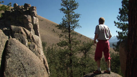 A man steps up onto a boulder and looks into the distance Stock Video Footage