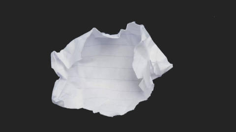 A crumpled piece of paper flattens out Footage