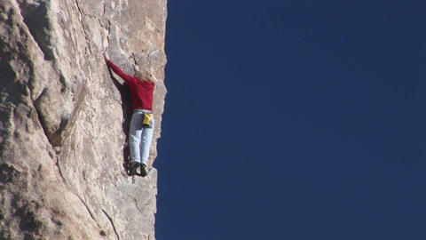 A woman climbs up the side of a mountain Footage