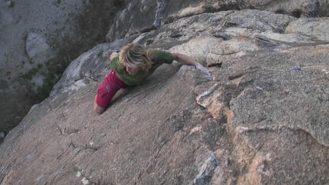 A young man climbs the side of a mountain Stock Video Footage