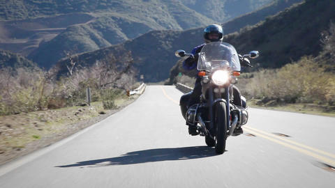 A man rides a motorcycle on a mountain road Stock Video Footage