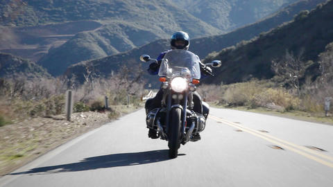 A man rides a motorcycle on a mountain road Footage