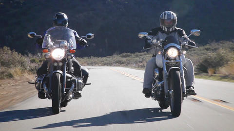 Two people ride motorcycles out in the country Stock Video Footage
