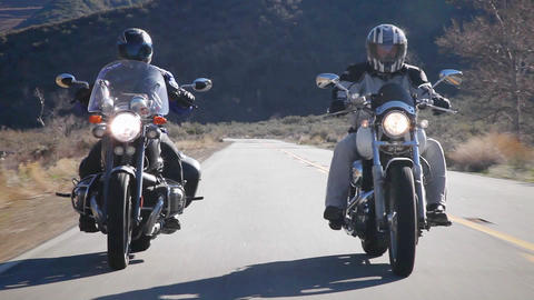 Two people ride motorcycles out in the country Footage