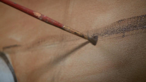 A paintbrush applies strokes of paint to an object Stock Video Footage