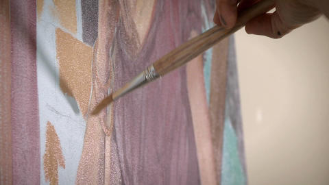 An artist works on a painting on their easel Footage