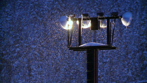 Snow falls at night through beaming flood-lights Footage