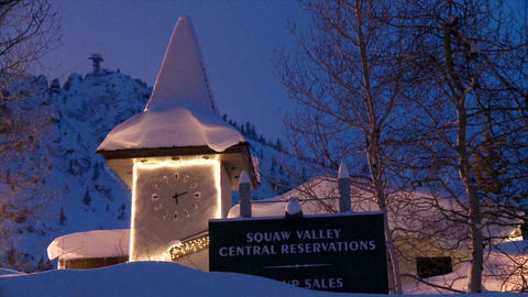 A hillside clock and sign structure is illuminated in the snowy evening Footage