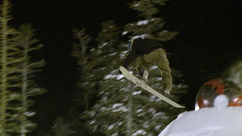 A snowboard rider hits a jump at night Footage