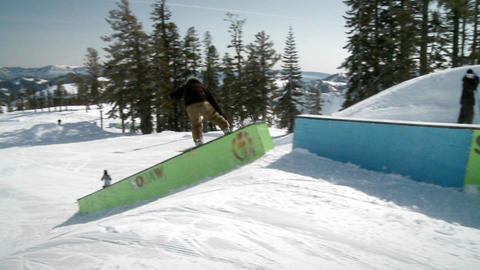 A snow boarder jumps up onto and slides down a long ramp Footage