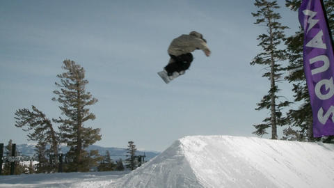 A snowboarder makes a jump off a large pile of snow Footage