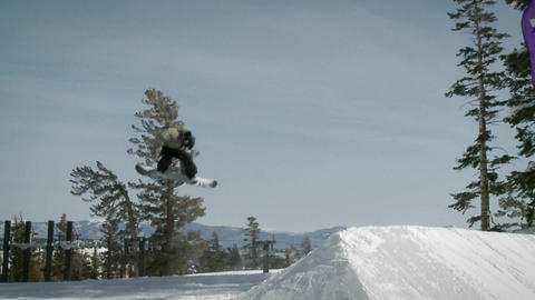 A snowboarder makes a jump off a large pile of snow Stock Video Footage