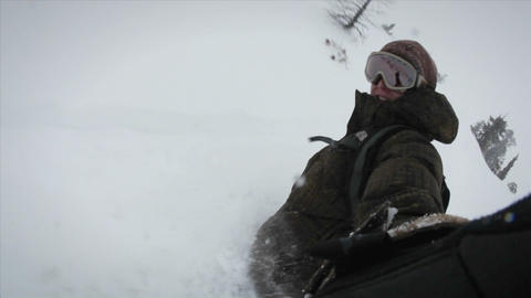 A snow-boarder records himself while boarding down a slope Footage