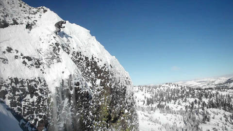 A skier jumps off the side of a mountain, and another person sits below Footage