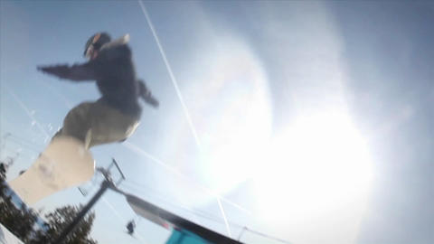 A snow-boarder slides on the edge of a long wall Stock Video Footage