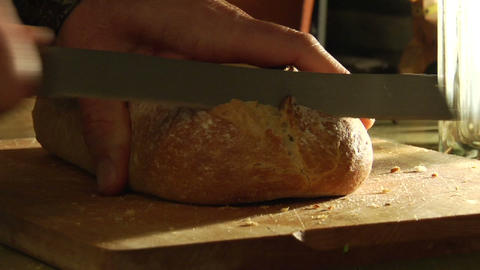Hands slice loaves of bread Live Action
