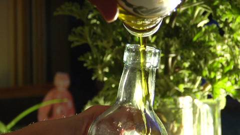 A man pours olive oil into a bottle Stock Video Footage