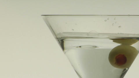 A green olive is dropped into a martini Footage