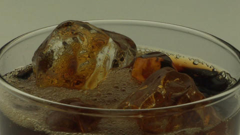 Amber-colored liquid is poured over ice into a glass Stock Video Footage