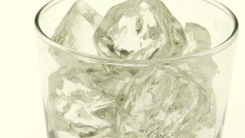 Dark, carbonated liquid is poured over ice into a glass Stock Video Footage