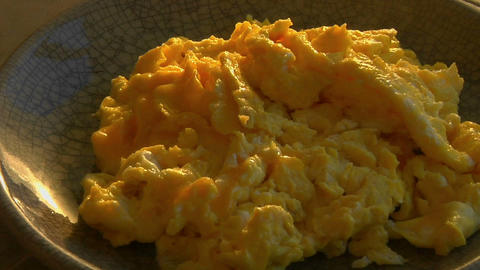 A slow pull into a bowl of scrambled eggs Stock Video Footage