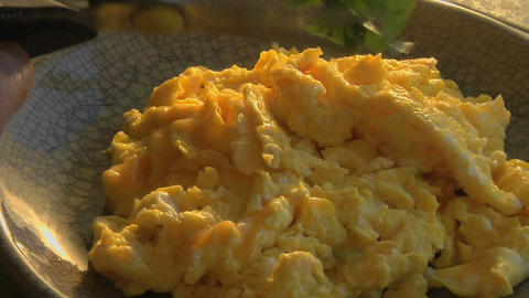 A slow pull into a bowl of scrambled eggs as parsley is... Stock Video Footage
