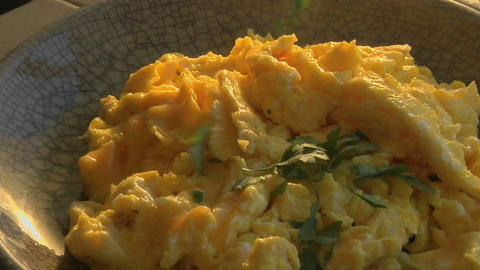 A slow pull into a bowl of scrambled eggs as parsley is chopped Footage