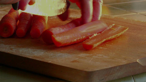 A chef slices carrots with a knife Footage