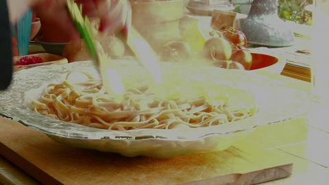 A Woman Chef Prepares A Meal By Pouring Fresh Cooked Pasta Into A Glass Bowl stock footage