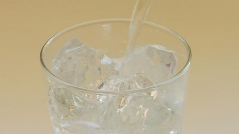 Clear sparkling water poured over ice cubes in a clear glass tumbler Footage